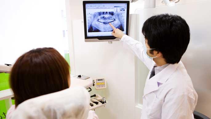 レントゲン写真を指さしながら根尖性歯周炎について説明している男性歯科医師