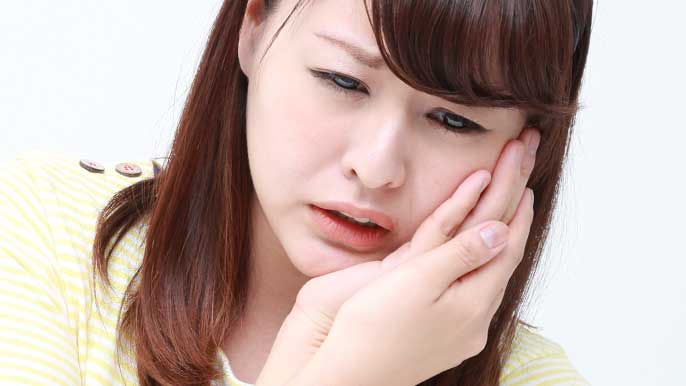 頬に手をあてて歯の痛みを我慢している女性