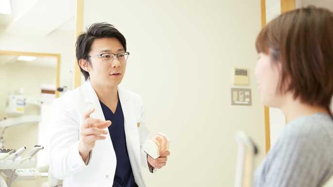 根管治療について説明している男性歯科医師