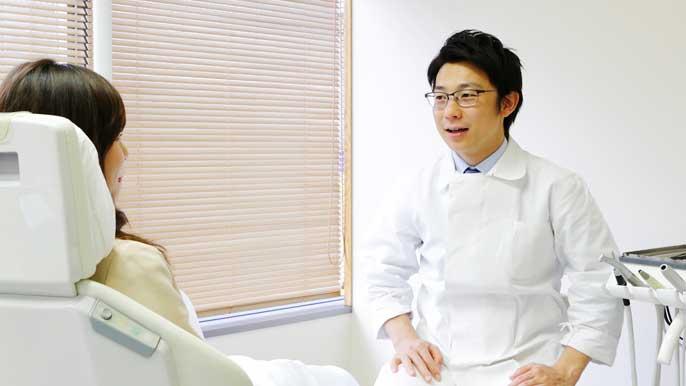 精密根管治療について説明している男性歯科医師