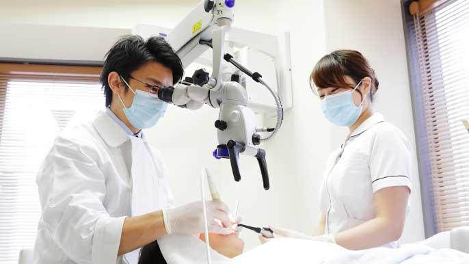 マイクロスコープを使って精密根管治療を行う男性歯科医師